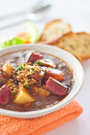 A bowl of hot steaming beef stew on orange cloth served with slices of garlic toast  Stock Photo