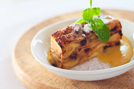 Baked bread pudding with raisins baked in creamy egg custard served with warm vanilla sauce and sugar  Stock Photo