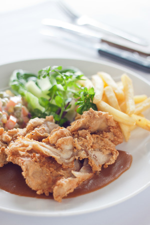 Deep fried chicken chop in seasoned flour served with french fries on big white plate