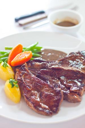 Gebratene Lammkoteletts mit frischen Möhren, Kartoffeln, Bohnen und braunen Sauce auf großen weißen Teller serviert Standard-Bild - 26591465