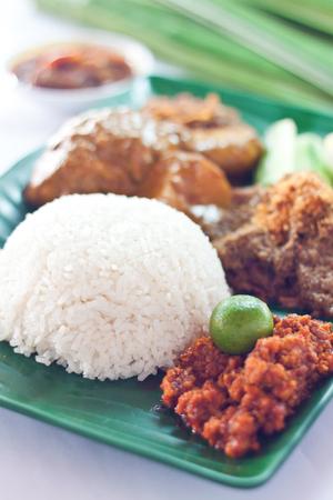 Malaysian traditional spicy dish hot steamed rice nasi lemak served with sambal belacan, ikan bilis, acar, peanuts and cucumber