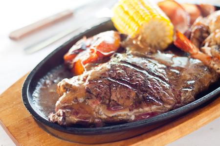 Gegrilltes Rindersteak auf einem heißen glühender Platte mit Mais, Tomaten, Garnelen und große braune Soße Standard-Bild - 26591486