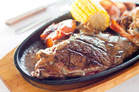 Grilled beef steak served on a hot sizzling plate with sweet corn, tomatoes, big prawns and brown sauce