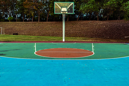 outdoor basketball court in the park  with trees  background