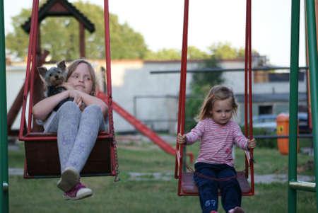 Two little girls on the swings side by side