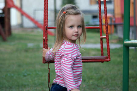 Little girl standing next to the swings Stock Photo