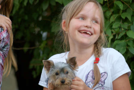 8 year old girl: 8 year old girl on a background of green leaves smiling with a dog on your hands