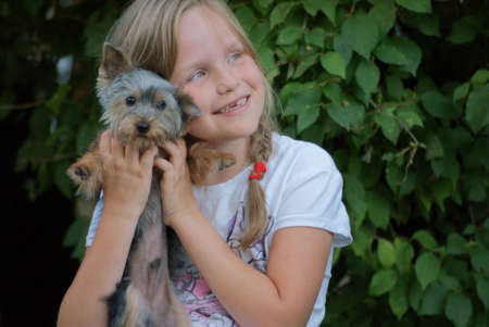 8 year old girl on a background of green leaves smiling with a dog on your hands