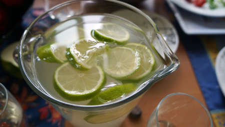Tasty drink in a vessel standing on the table  With green lemons