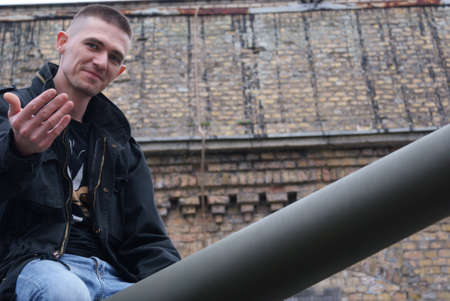 civilian: Young man sitting on a barrel of a tank  Civilian  Stock Photo