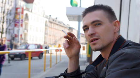 Young man smoking a cigarette  City, on the outside                            Stock Photo