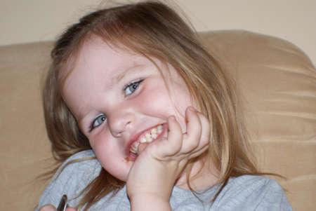 ashamed: A young girl smiles and ashamed.