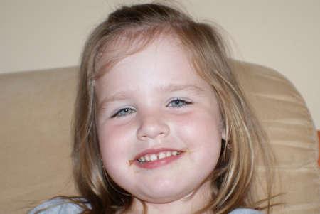A young girl smiles.