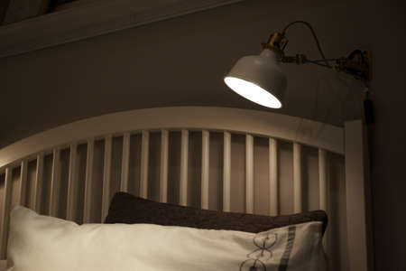 bed frame: Lighting the lamp over the bed frame.