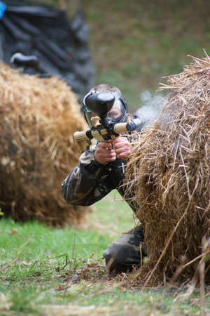 Paintball, a man aiming a player, leans out from behind cover. Stock Photo