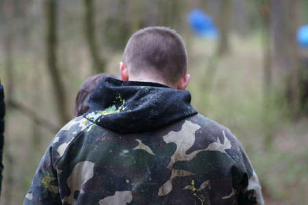 Paintball player standing back.