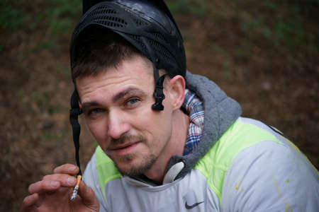 Paintball player smokes a cigarette and looks at the camera. Mask swept back. Stock Photo