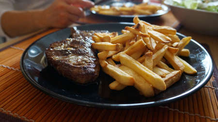 Tasty steak with french fries on a plate. Stock Photo