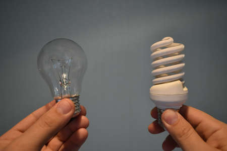incandescent bulb and energy saving in hand on empty background Stock Photo