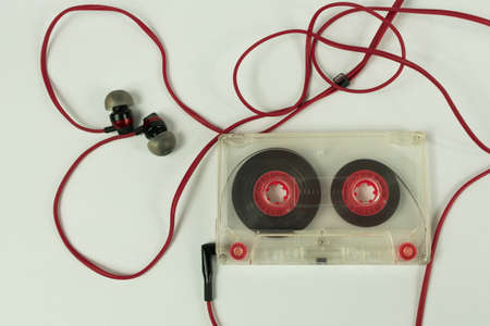 Transparent audiocassette surrounded by a cord of headphones in the shape of a heart on a white background Stock Photo