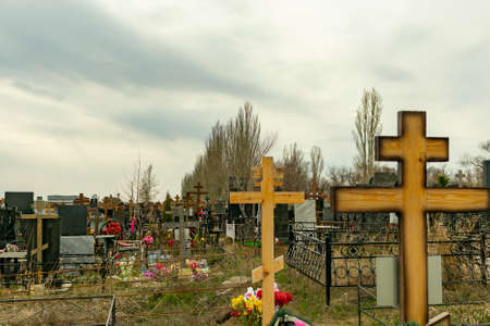Russian cemetery with wooden orthodox crosses and flowers on graves behind fences, in the spring against a cloudy sky Stock Photo