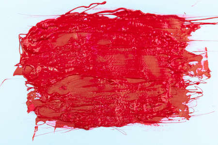 textured red color, smeared on a wall on a white background