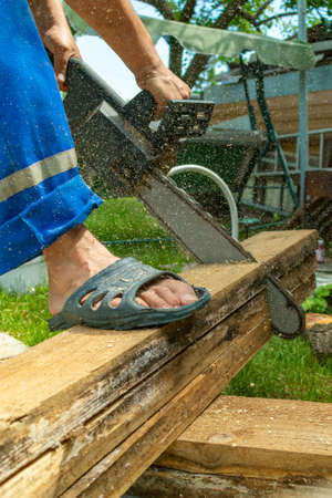 a man in working overalls cuts pine boards with an electric hand saw, standing in slippers