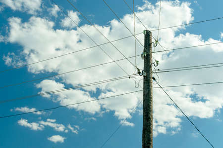 old wooden power post column entangled with live wires against the blue sky with clouds
