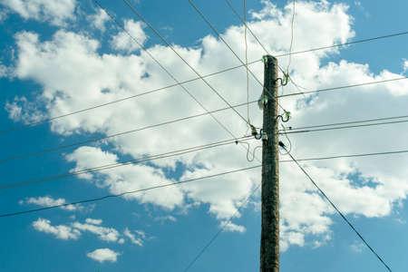 alte hölzerne Kraftpfostensäule, verwickelt mit stromführenden Drähten gegen den blauen Himmel mit Wolken Standard-Bild
