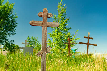 old wooden crosses on abandoned graves in the cemetery, overgrown with grass and trees