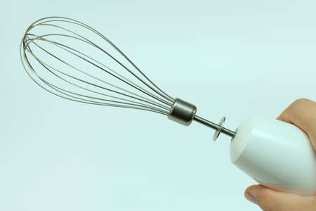 metal whisk mixer for beating in hand, on blue background, close-up