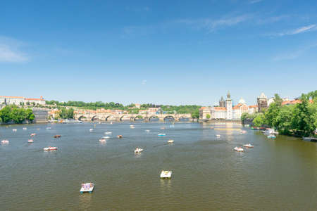 catamarans with resting tourists floating on the river at the Charles Bridge, in the historic center of the city