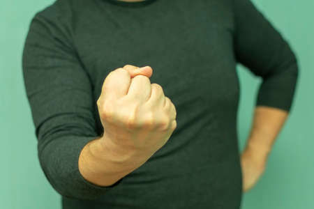 clenched fist as a sign of aggression and the threat of being beaten