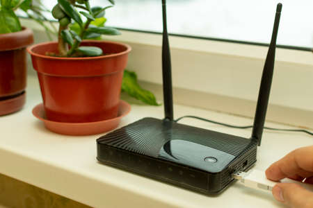 insert a mobile usb modem into the Internet router on the window sill by the window Banco de Imagens - 121240247