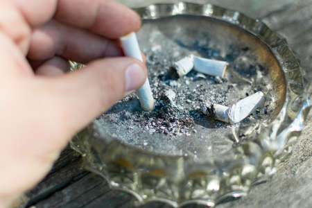 put out a burning cigarette in an ashtray with cigarette butts