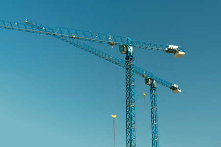 couple of building cranes on sky background