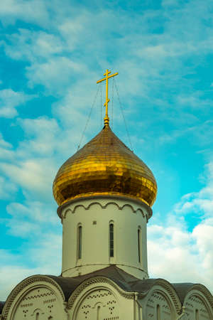 gilded dome with a cross of an old church against the blue sky