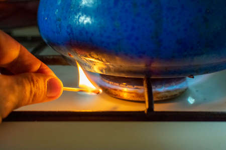 A man lighting the gas-stove with a match Imagens