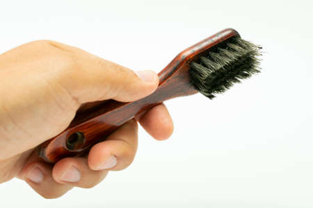 shoe polish brush in hand on white background