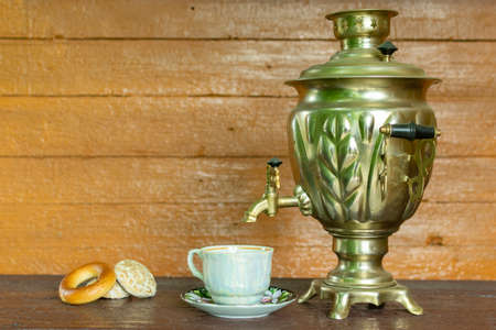 Russian traditional vessel for tea drinking, a samovar, on a table with a cup next to it and gingerbread and cookies Banco de Imagens