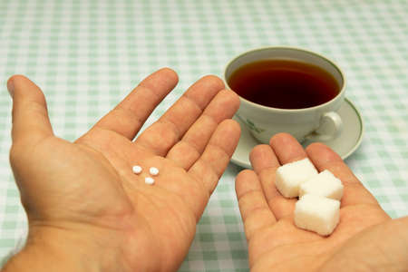 three small sweetener tablets replacing three teaspoons of sugar in hand for adding to a cup of tea