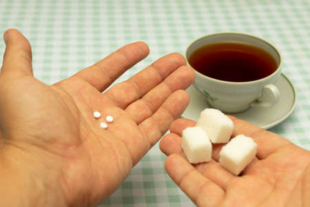 three small sweetener tablets replacing three teaspoons of sugar in hand for adding to a cup of tea Stockfoto