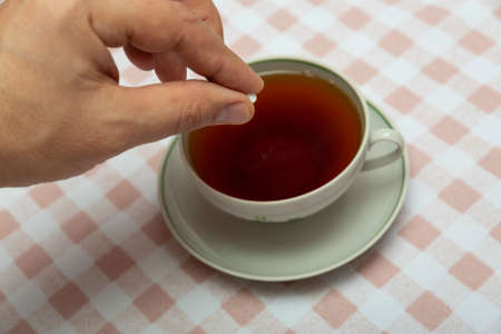 put a small tablet of sugar substitute in a cup of tea