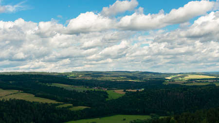 summer landscape, cloudy blue sky and green fields with forests