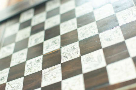 Chess board background. Handmade chessboard assembled from pieces of different wood