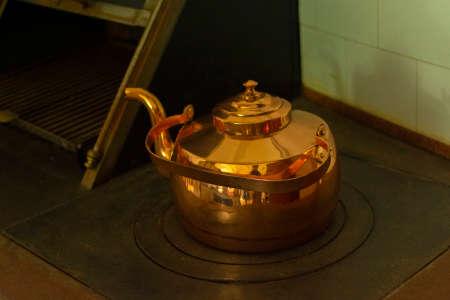 large antique copper teapot on the stove Standard-Bild
