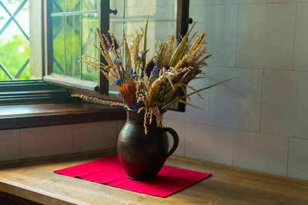 dry bouquet of evil and flowers in a vase on a red cupboard on the table, in the kitchen
