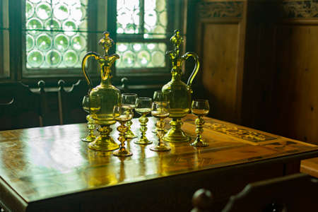 glass glasses and decanters for wine and drinks on a wooden table Standard-Bild