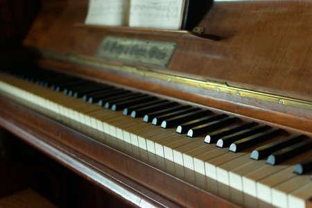 Closeup of black and white piano keys and wood grain with sepia tone Standard-Bild
