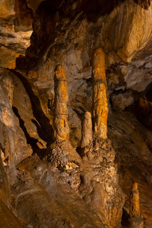 inside a karst cave with various ancient stalactites and stalagmites from salts and minerals, as a background